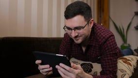 Νεαρός άνδρας με τον υπολογιστή ταμπλετών που βρίσκεται διαβασμένες στις καναπές αστείες ειδήσεις απόθεμα βίντεο