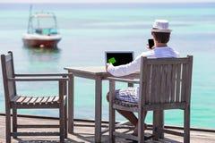 Νεαρός άνδρας με τον υπολογιστή ταμπλετών στην τροπική παραλία Στοκ φωτογραφία με δικαίωμα ελεύθερης χρήσης