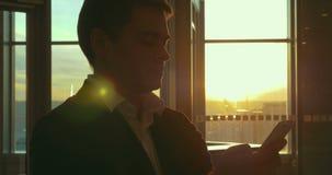 Νεαρός άνδρας με το έξυπνο τηλέφωνο στον αερολιμένα απόθεμα βίντεο