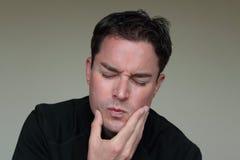 Νεαρός άνδρας με το επίπονο πρόσωπο λόγω του πονόδοντου Στοκ Φωτογραφία