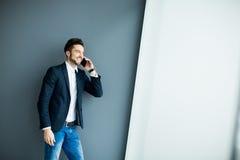 Νεαρός άνδρας με το κινητό τηλέφωνο από τον τοίχο Στοκ Φωτογραφίες