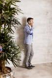 Νεαρός άνδρας με το κινητό τηλέφωνο από τον τοίχο Στοκ Εικόνα
