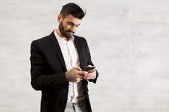 Νεαρός άνδρας με το κινητό τηλέφωνο από τον τοίχο Στοκ Εικόνες