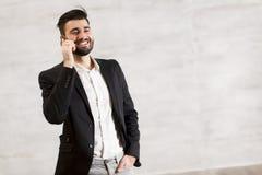 Νεαρός άνδρας με το κινητό τηλέφωνο από τον τοίχο Στοκ φωτογραφία με δικαίωμα ελεύθερης χρήσης