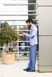 Νεαρός άνδρας με το κινητό τηλέφωνο με το κτίριο γραφείων Στοκ φωτογραφία με δικαίωμα ελεύθερης χρήσης