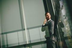 Νεαρός άνδρας με το κινητό τηλέφωνο με το κτίριο γραφείων Στοκ φωτογραφίες με δικαίωμα ελεύθερης χρήσης