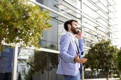 Νεαρός άνδρας με το κινητό τηλέφωνο με το κτίριο γραφείων Στοκ εικόνα με δικαίωμα ελεύθερης χρήσης