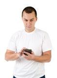 Νεαρός άνδρας με το κινητό τηλέφωνο που απομονώνεται σε ένα λευκό Στοκ Φωτογραφίες