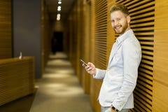 Νεαρός άνδρας με το κινητό τηλέφωνο στην αρχή Στοκ φωτογραφίες με δικαίωμα ελεύθερης χρήσης