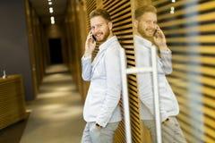 Νεαρός άνδρας με το κινητό τηλέφωνο στην αρχή Στοκ φωτογραφία με δικαίωμα ελεύθερης χρήσης