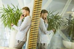 Νεαρός άνδρας με το κινητό τηλέφωνο στην αρχή Στοκ εικόνα με δικαίωμα ελεύθερης χρήσης