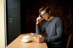 Νεαρός άνδρας με το κινητό τηλέφωνο στη καφετερία Στοκ φωτογραφίες με δικαίωμα ελεύθερης χρήσης