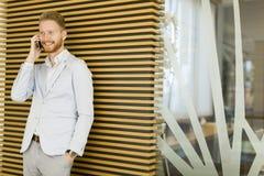 Νεαρός άνδρας με το κινητό τηλέφωνο στο γραφείο Στοκ Εικόνες