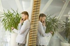 Νεαρός άνδρας με το κινητό τηλέφωνο στο γραφείο Στοκ φωτογραφίες με δικαίωμα ελεύθερης χρήσης