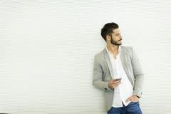 Νεαρός άνδρας με το κινητό τηλέφωνο στο γραφείο Στοκ εικόνες με δικαίωμα ελεύθερης χρήσης