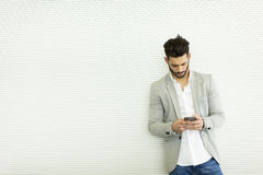 Νεαρός άνδρας με το κινητό τηλέφωνο στο γραφείο Στοκ Φωτογραφία