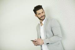Νεαρός άνδρας με το κινητό τηλέφωνο στο γραφείο Στοκ φωτογραφία με δικαίωμα ελεύθερης χρήσης