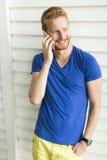 Νεαρός άνδρας με το κινητό τηλέφωνο υπαίθριο Στοκ Φωτογραφίες