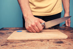 Νεαρός άνδρας με το μαχαίρι και τεμαχίζοντας πίνακας Στοκ φωτογραφία με δικαίωμα ελεύθερης χρήσης
