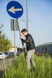Νεαρός άνδρας με το οδικό σημάδι στη μακριά χλόη ακρών του δρόμου Στοκ Εικόνα