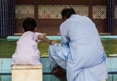 Νεαρός άνδρας με το παιδί του που παίρνει έτοιμο για τις προσευχές. Στοκ εικόνες με δικαίωμα ελεύθερης χρήσης