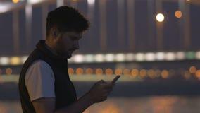Νεαρός άνδρας με το τηλέφωνο που εξετάζει τη γέφυρα του Περθ, ο μεγάλος, ποταμός Neva απόθεμα βίντεο