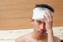 Νεαρός άνδρας με το τραύμα του κεφαλιού από τον ιατρικό επίδεσμο Στοκ Φωτογραφία