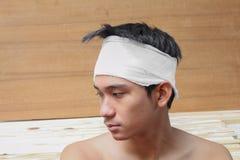 Νεαρός άνδρας με το τραύμα του κεφαλιού από τον ιατρικό επίδεσμο Στοκ Φωτογραφίες