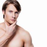Νεαρός άνδρας με το χέρι κοντά στο πρόσωπο Στοκ Εικόνα
