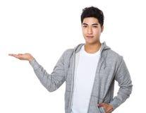 Νεαρός άνδρας με το χέρι που παρουσιάζει κενό σημάδι Στοκ εικόνα με δικαίωμα ελεύθερης χρήσης