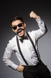 Νεαρός άνδρας με το ψεύτικο moustache που απομονώνεται σε γκρίζο Στοκ Εικόνα