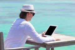 Νεαρός άνδρας με το lap-top στην τροπική παραλία Στοκ φωτογραφία με δικαίωμα ελεύθερης χρήσης