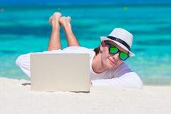 Νεαρός άνδρας με το lap-top στην τροπική παραλία Στοκ εικόνες με δικαίωμα ελεύθερης χρήσης