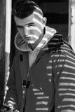 Νεαρός άνδρας με το smartphone υπαίθριο που καλύπτει με τη σκιά φωτός του ήλιου Στοκ Φωτογραφίες