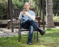 Νεαρός άνδρας με χυτό βραχίονας στο τηλέφωνό του Στοκ φωτογραφίες με δικαίωμα ελεύθερης χρήσης