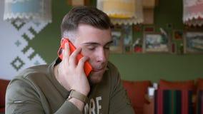 Νεαρός άνδρας που έχει μια συνομιλία τηλεφωνήματος στο εστιατόριο απόθεμα βίντεο