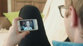 Νεαρός άνδρας που έχει μια τηλεοπτική συνομιλία συνομιλίας στο smartphone του με τη νέα γυναίκα hipster απόθεμα βίντεο