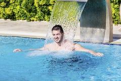 Νεαρός άνδρας που έχει τη διασκέδαση με το νερό στην πισίνα Στοκ εικόνες με δικαίωμα ελεύθερης χρήσης