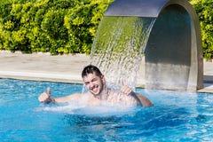Νεαρός άνδρας που έχει τη διασκέδαση με το νερό στην πισίνα Στοκ Φωτογραφίες