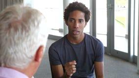 Νεαρός άνδρας που έχει τη σύνοδο παροχής συμβουλών απόθεμα βίντεο