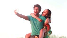Νεαρός άνδρας που δίνει στη φίλη του έναν γύρο σηκώνω στην πλάτη παίρνοντας selfie φιλμ μικρού μήκους