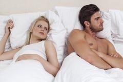 Νεαρός άνδρας που αγνοεί τη γυναίκα στο κρεβάτι Στοκ εικόνα με δικαίωμα ελεύθερης χρήσης