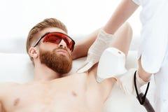 Νεαρός άνδρας που λαμβάνει τη φροντίδα δέρματος λέιζερ στη μασχάλη που απομονώνεται στο λευκό στοκ φωτογραφία