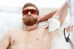 Νεαρός άνδρας που λαμβάνει τη φροντίδα δέρματος λέιζερ στη μασχάλη που απομονώνεται στο λευκό Στοκ Φωτογραφίες
