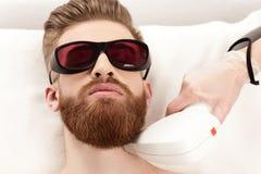 Νεαρός άνδρας που λαμβάνει τη φροντίδα δέρματος λέιζερ στο λαιμό στοκ εικόνα