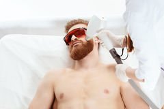 Νεαρός άνδρας που λαμβάνει τη φροντίδα δέρματος λέιζερ στο πρόσωπο που απομονώνεται στο λευκό Στοκ Φωτογραφία