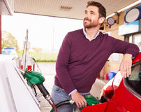 Νεαρός άνδρας που ανεφοδιάζει σε καύσιμα ένα αυτοκίνητο σε ένα πρατήριο καυσίμων Στοκ Φωτογραφίες