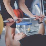 Νεαρός άνδρας που ανυψώνει το barbell στη γυμναστική με τον εκπαιδευτικό Στοκ φωτογραφίες με δικαίωμα ελεύθερης χρήσης