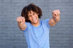 Νεαρός άνδρας που γελά και που δείχνει τα δάχτυλα Στοκ Εικόνες