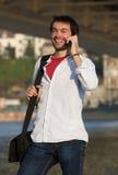Νεαρός άνδρας που γελά με το κινητό τηλέφωνο υπαίθρια Στοκ φωτογραφία με δικαίωμα ελεύθερης χρήσης